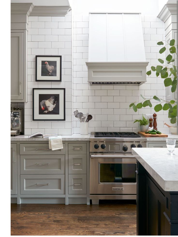 Subway tile, grey cabinets, dark colored island, carrera marble