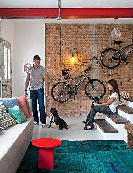 Na entrada da casa, os moradores Phil Chaves e a noiva, Carolina Rosas, brincam com o casal de buldogues franceses. Na parede de tijolos aparentes, a grade acomoda bicicletas, chaves, capacetes e bonés. Uma luminária ainda dá destaque ao cantinho