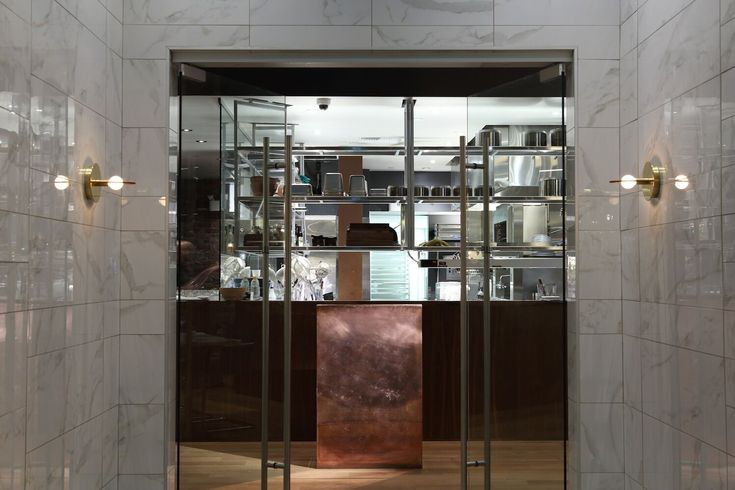 """An integrated iPad fits right into the custom copper host deck at the entrance of the restaurant. """"I think I'm having a moment with copper,"""" says Greenway. """"It's wearing in and oxidizing, right behind is stainless steel shelving."""""""