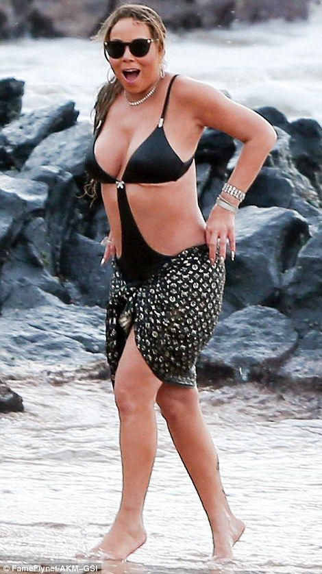 Daring to bare: Mariah turned heads in a plunging black swimsuit with cut-out sides
