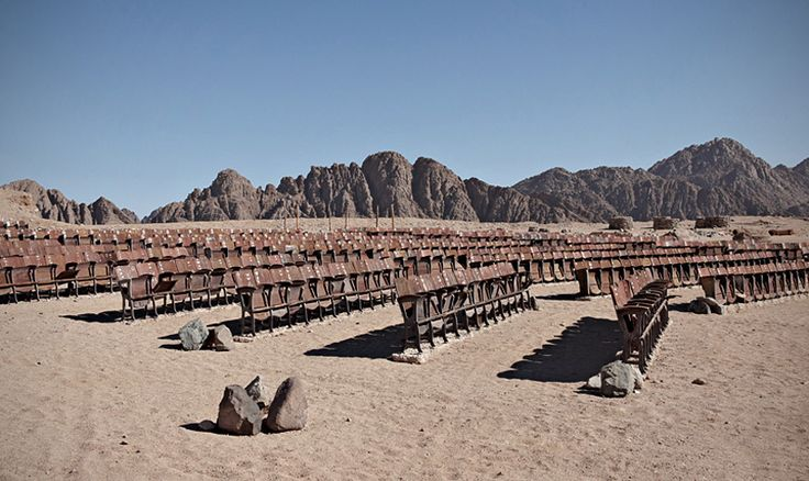 an abandoned movie theater lays in the middle of the egyptian desert
