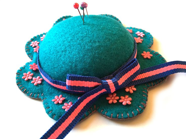 "Teal felt hat pin cushion Stuffed it with a polyester fiber fill. The pin cushion measures 5"" wide and only 1 1/2"" tall. The actual pin cushion area is 3 1/8""."