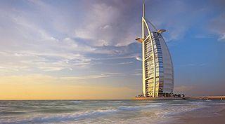 """O Burj el Arab tem fachada imponente , na forma de """"vela de barco"""" , com todas as comodidades dignas de um """" hotel sete estrelas"""" , ESTÁ CLASSIFICADO COMO O MAIS CARO E LUXUOSO DO PLANETA ."""
