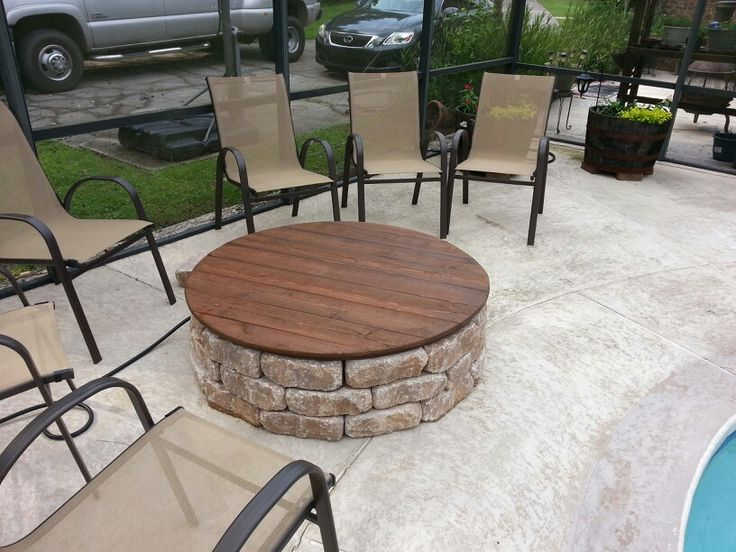 This is our firepit with a gas insert and a wooden cover that doubles as a table on warm days. The cover is plywood with cedar planks glued and tacked to it. We put waterproof sealer on it in a chocolate color.