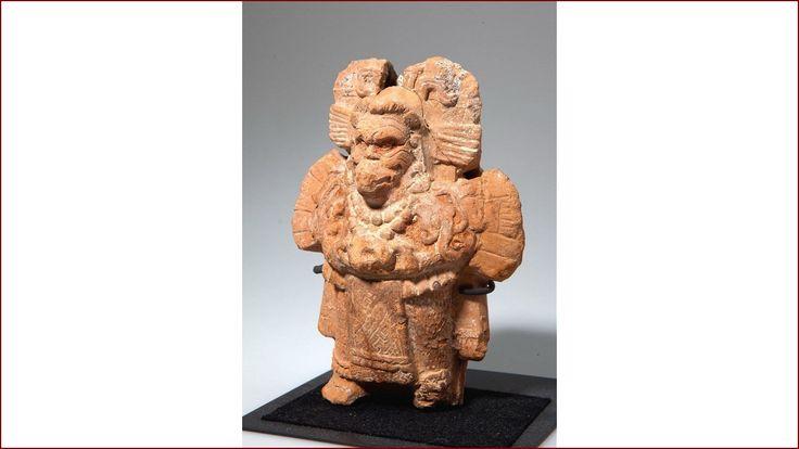 Dit is een god of priesterfiguur met rookpluimen uit het hoofd. Op zijn gezicht, of masker, dat lijkt op een brulaap zijn rimpels of tatoeages te zien. In zijn handen draagt hij een spiegel. Spiegels hebben een speciale betekenis in Midden-Amerika. Ze vormen een doorgangsweg naar de Andere Wereld, ook worden ze geïdentificeerd met de zon en de maan. De godheid houdt de spiegel voor zijn navel, het centrum van het lichaam, de stuwende kracht van de mens.