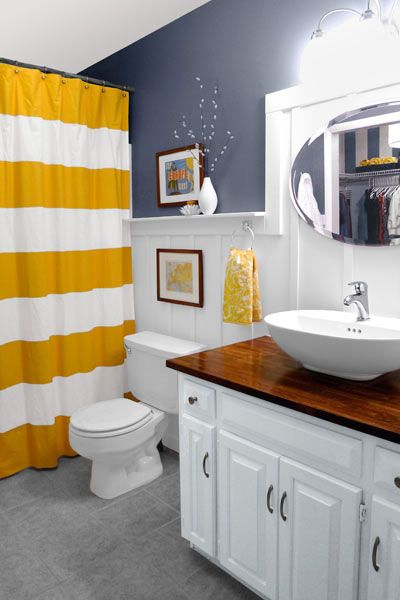 board and batten wainscotting lines the walls of this white and steel-grey bathroom, with a bold, horizontally-striped yellow and white shower curtain in the back