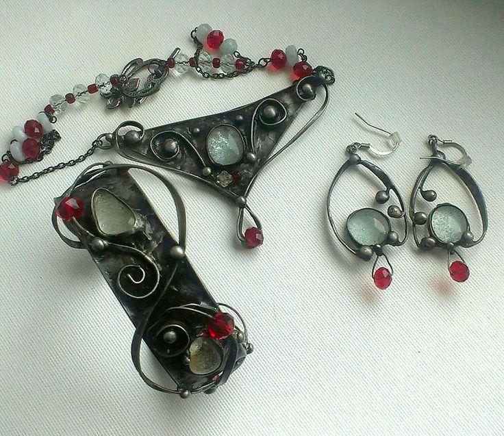 Cínovaný šperk ozdobený broušenými červenými korálky a skleněnými kabošony, které ve tmě svítí. Z autorské dílny Qtáček.