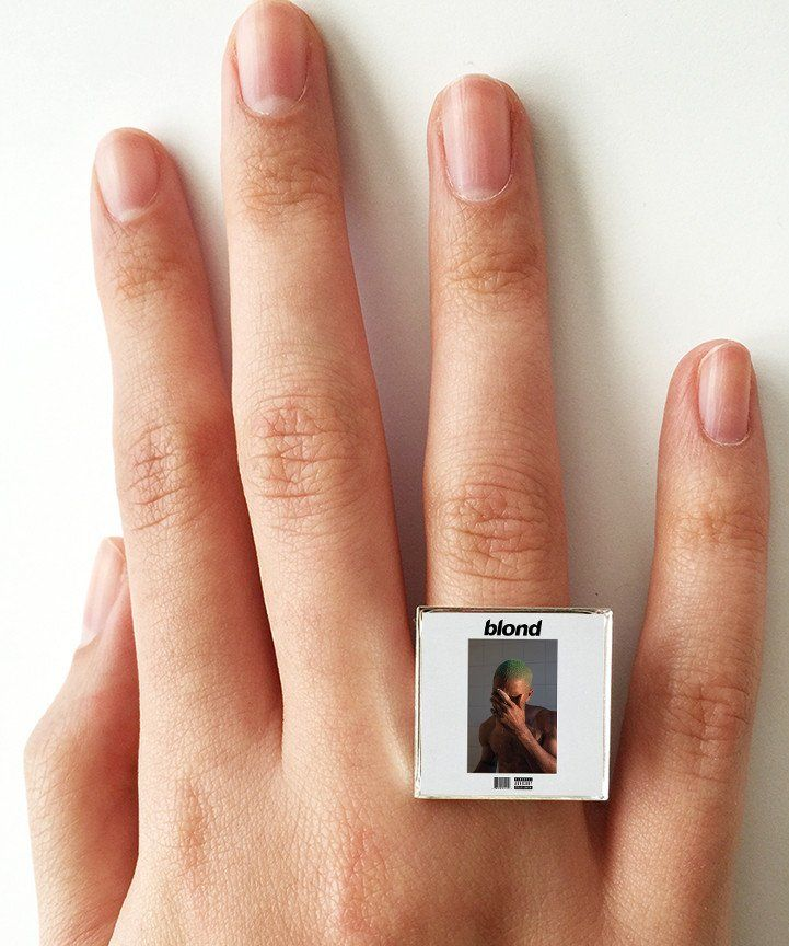 """This is a ring featuring album art of the """"Blonde"""" (or Blond) record by Frank Ocean sealed in a silvertone metal setting. The album cover ring measures 3/4"""" at the front, is adjustable in size and is"""