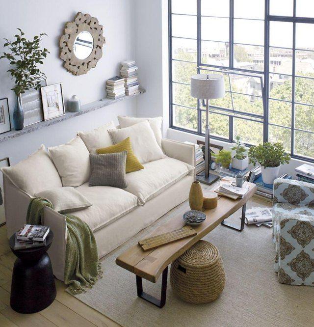 petit salon clair avec canapé rembourré,table en bois rustique et plantes vertes