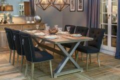 Komplet krzeseł ze stołem na 6 osób. Solidny drewniany stół w kształcie prostokąta o skrzyżowanych nogach połączonych belką biegnącą pod blatem stołu. Krzesła tapicerowane z ozdobnymi pinami i uchwytem na oparciu. Krzesła prostymi, drewnianymi nogami.