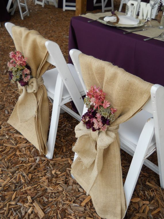 A wide length of fabric with a tie and flowers for chairs