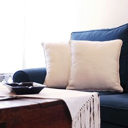 Blue couch with neutral textiles and cushion covers. Timeless decor.