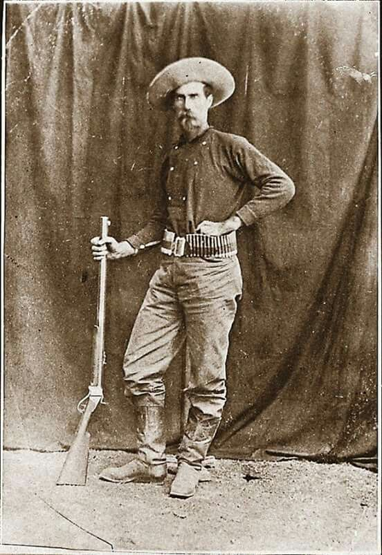 1870's buffalo hunter with 1874 Sharps rifle with double triggers. Bib front shirt tucked into pants.
