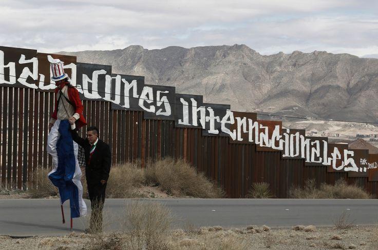 Le président mexicain, Enrique Peña Nieto donne la main à un manifestant déguisé en Oncle Sam pour protester contre le projet de mur anti-clandestins le long de la frontière avec les Etats Unis, le 26 février 2017 à Ciudad Juarez. On peut lire sur la barrière de séparation: « Ni délinquants, ni clandestins, nous sommes des travailleurs internationaux.». /  Christian Torres/AP