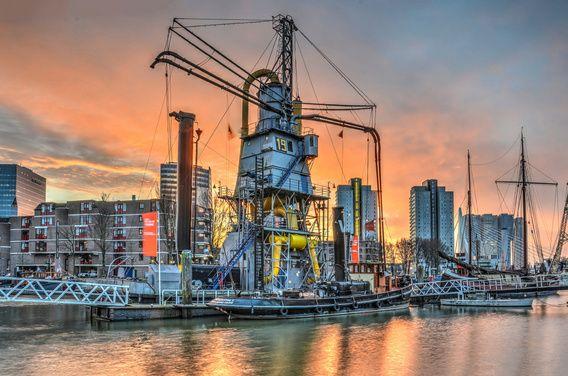 Rotterdam: Leuvehaven onder een rode hemel - De Leuvehaven is een van de oudste havens van Rotterdam en is tegenwoordig in gebruik als buitenexpositie van het Maritiem Museum. Een van de pronkstukken van de collectie, hier te zien onder een bloedrode hemel kort voor zonsopkomst, is een graanelevator waarmee in vroeger tijden graanschepen gelost werden.  Rechts op de achtergrond is de Kop van Zuid te zien met de Erasmusbrug en De Rotterdam