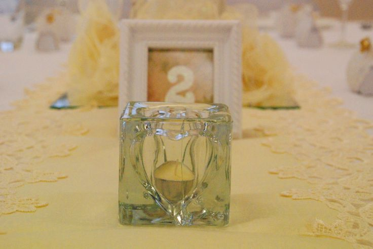 Thick Glass Heart Tealight Candle Holders with Vintage Framed Table Numbers on a elegant cream lace embroidered table runner