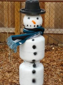Snowman from propane tanks and deflated basketball for his head.