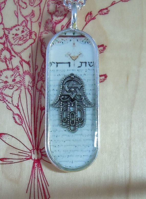 No connection to this Hamsa symbol, but this is a great example of the ice resin jewelry Im working on now.  You get a resevoir/holder like this silver one here, put in a back ground (I like tea stained poems or scriptures, myself), fill the holder halfway with the resin, add an item, fill the rest of the way up...and voila!