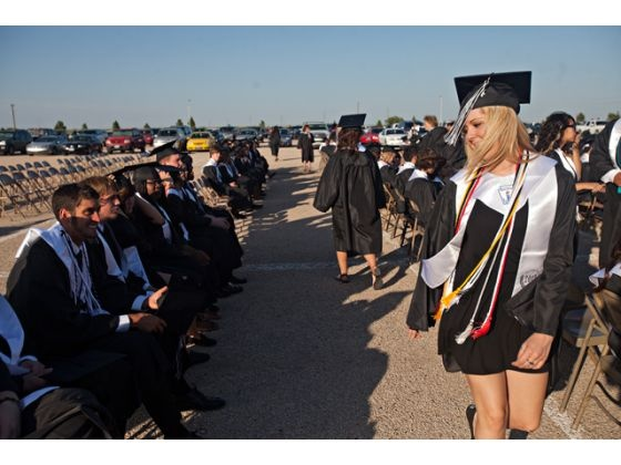 'Connor Stevens, left, smiles Friday at Mallory Widener, right, after greeting her as she walks by while waiting for the Permian High School Class of 2012 Graduation Ceremony at Ratliff Stadium.' Photo by Albert Cesare for Odessa American