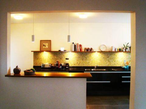 Com 15 m², esta cozinha projetada pelo arquiteto Alexandre Freitas dos Santos tem balcão feito de chapa de compensado revestida de madeira apoiada na alvenaria. Duas cadeiras se posicionam do lado interno do balcão e a parede do fundo é revestida de pastilhas de vidro.