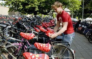 Un jeune homme recouvre des selles de vélo d'une protection rouge dans le cadre…