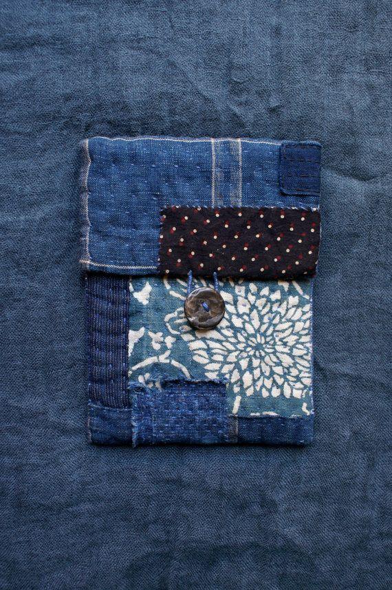 pochette entièrement cousue et brodée à la main, en tissus japonais anciens : katazome , aizome, kasuri... cette pochette a été inspirée par lart du recyclage Japonais : le boro... les tissus extérieurs sont en coton teint à lindigo naturel selon les techniques traditionnelles et le tissu intérieur est en coton de kimono yukata vintage noir et blanc-cassé à carreaux patch noir à petits pois en coton blockprinted du Rajasthan le rembourrage intérieur est 100 % coton cette pochette ferme…