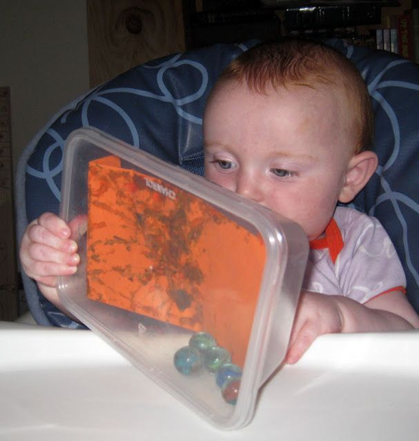 Allow infants to explore the effects of handling a covered plastic containter filled with paint, paper, and marbles