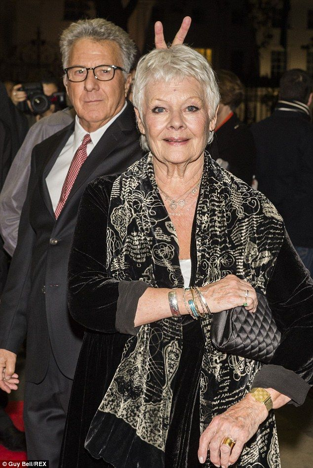 Photobombed: Dame Judi Dench is surprised by a cheeky Dustin Hoffman on the red carpet