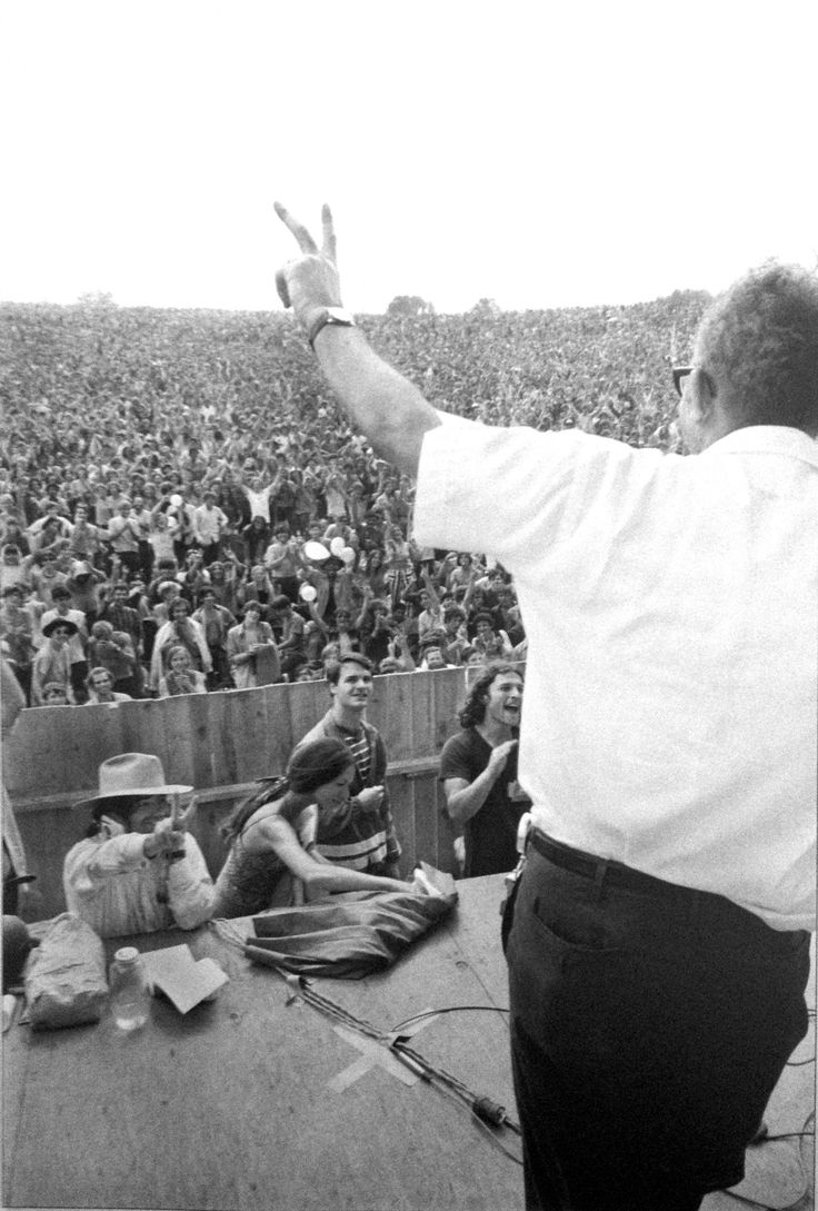 """Max Yasgur addressing the crowd 44 years ago today. Martin Scorses returning the peace sign in the bottom left.   """"This is the largest group of people ever assembled in one place, and I think you people have proven something to the world: that a half a million kids can get together and have three days of fun and music and have nothing but fun and music, and I God bless you for it!"""""""
