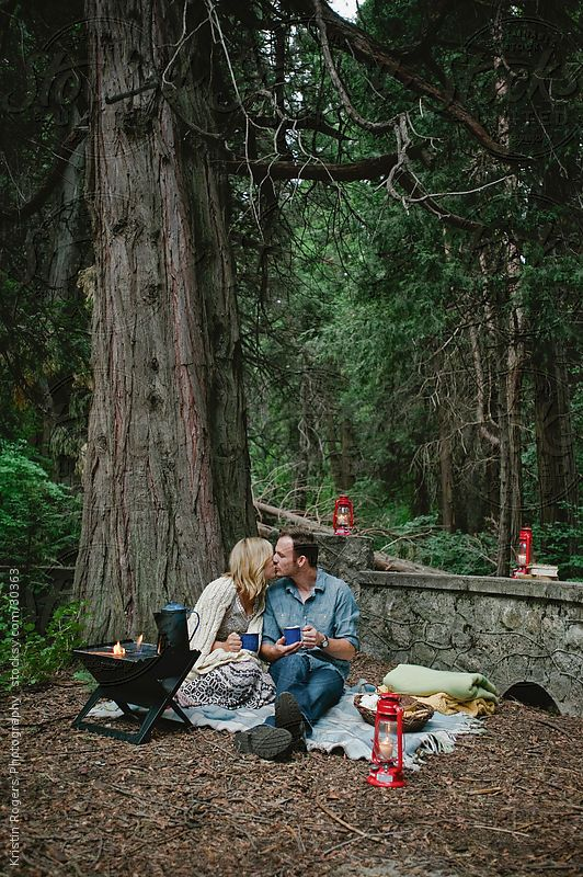 Couple sitting in forest on a camping date. | Romantic ...