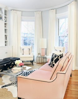 Room Run Down: Layered rugs- Faux zebra over natural jute rug- High Gloss Mag- white curtains-Pink sofa with black contrasting trim- glass coffee table from Wisteria.