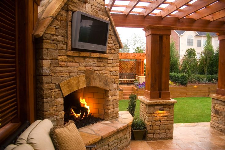 Outdoor Stacked Stone Fireplace With TV Mount With Attached Pergola.