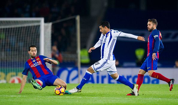 Sergio Busquets of FC Barcelona duels for the ball with Carlos Vela of Real Sociedad during the La Liga match between Real Sociedad de Futbol and FC...