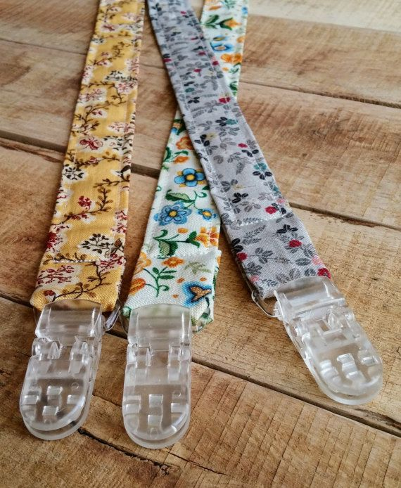 Keep your childs soother close by with this beautiful floral print universal soother clip/pacifier clip. Made with 100% cotton in a vintage style floral pattern.  It comes with an elastic on one end that loops through any soother clip or toy. On the other end it has a sturdy clip that attaches easily to clothing that cannot be removed by child. This universal soother clip is 1 wide and is 13 long. It is top stitched for durability  Makes a great toy strap as well! Easily attaches to toys...