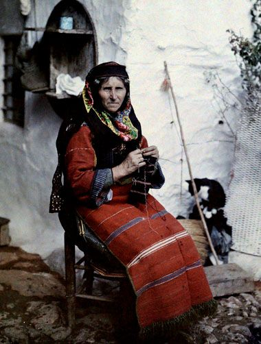 A woman in traditional Greek dress knits sitting outside her home, Aivali