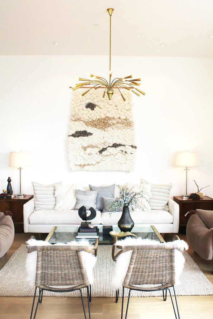 Seating nook with gold pendant light, chunky wall weaving, and sheepskin throws.