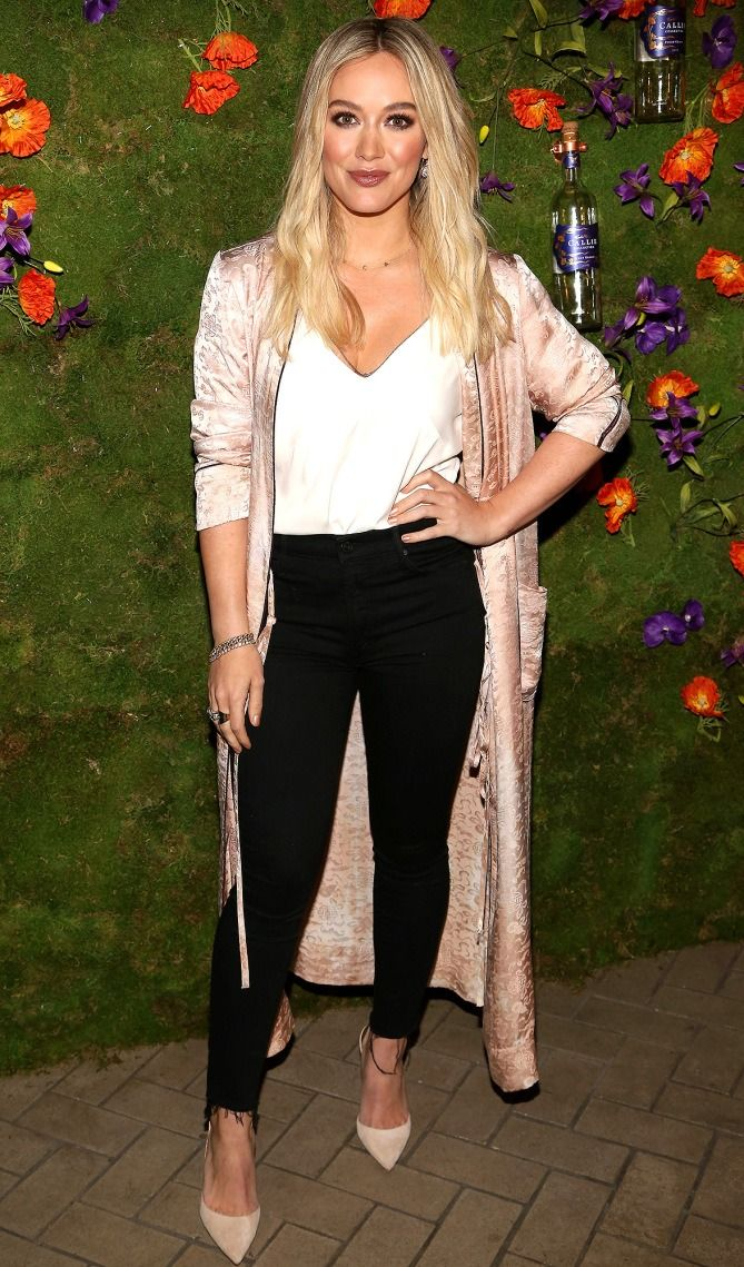 Hilary Duff in a white tank top, black jeans and pink satin duster coat