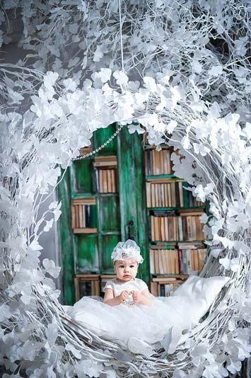 Фотография ребенка на качелях с книгами