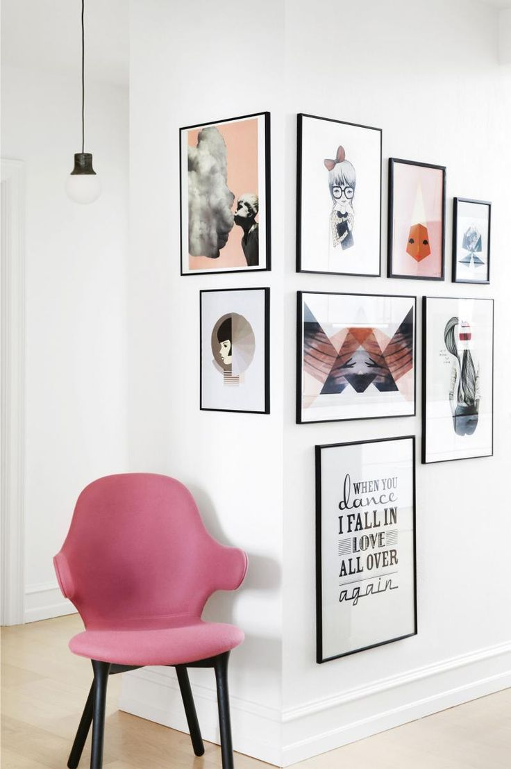 Gallery wall/corner: prints in black frames, white walls, pale floorboards, pink upholstered chair with black legs