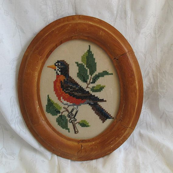 Charming cross stitched large robin in a striking rustic oval wood frame. Dimensions are 14 1/4 by 12 to the outside edge of the frame. Bird is about 6 1/2 inches tall. I just love the antique frame which looks to be hand made. Frame has glass. Nicely embroidered. Very good condition.