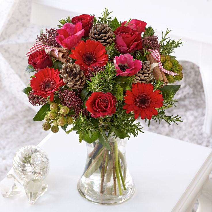 This elegant gift is perfect for Christmas, featuring red germini, red roses, red anemone and a red skimmia with galpini, pine cones, rosemary and cinnamon bundles.