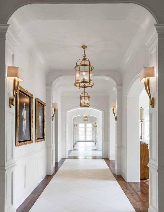 A long hallway features walls clad in wainscoting lined with kids' photos in gold baroque frames illuminated by antique brass sconces, Ruhlmann Single Sconces, as well as round brass lanterns, Round Edwardian Entry Lanterns.