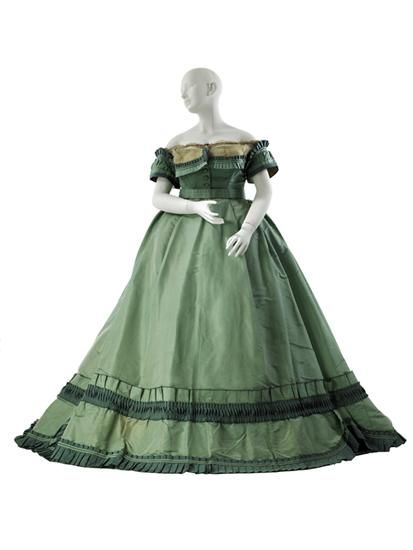 1864-67 This versatile day-into-evening dress, with its sophisticated color juxtaposition, provides an insight into the subtle considerations that defined Worth's designs. By providing his client a dress with both a day and evening bodice, he was able to justify his extraordinary pricing by maximizing a garment's wearability.