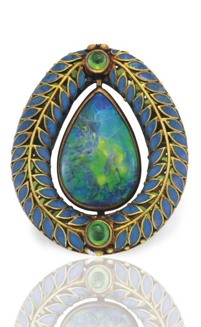 TIFFANY & CO. - AN ANTIQUE BLACK OPAL, DEMANTOID GARNET AND ENAMEL BROOCH, CIRCA 1910. Centring upon a pear-shaped black opal cabochon, within a sculpted gold and blue plique-à-jour enamel, accented by circular cabochon demantoid garnets, the reverse set with green plique-à-jour enamel, 1 5/16 ins. Signed Tiffany & Co. #Tiffany #antique