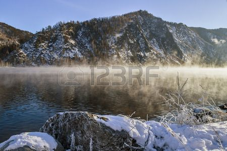 Yenisey River between the village of main and Cheremushki district. January 2014 onwards. Right, Rocky River Bank is reflected in the water. The river is covered with a mist.