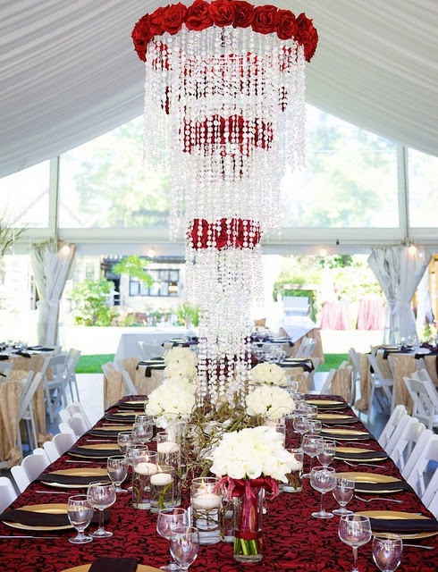 An elegant tuscany-style headtable with red roses, gold charger plates, and warm brown napkins.