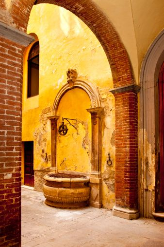 Inner courtyard water well in medieval town of Siena, Tuscany, Italy
