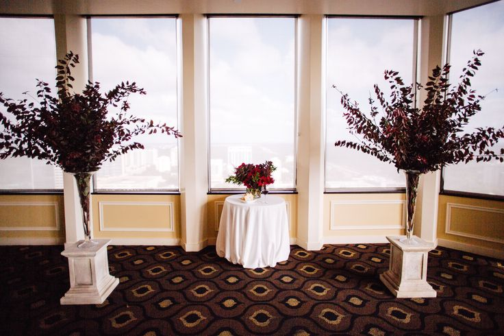 the modern wedding ceremony decor included a pair of tall trumpet vases filled with purple plum branches and a communion table with an arrangement of red, burgundy, plum and pink flowers.
