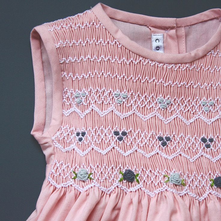 Coquito: Pink dress with white smocking and blue flowers and accents.