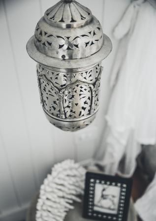Brass pendant light and decorator items sit at the bedside table of the main bedroom at The Grove Byron Bay